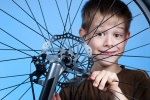 Boy is repairing the bicycle wheel