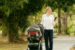 Beautiful woman walking down a lane in park with her little daughter in pushchair, text messaging on mobile phone and smiling. Full length view